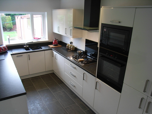 чёрная столешница в интерьере белой кухни