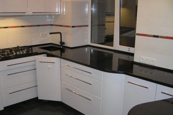 Чёрная плитка на полу в интерьере белой кухни
