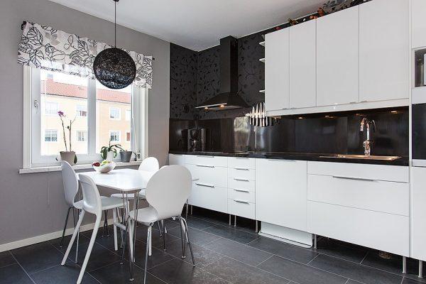 Белая кухня с черной столешницей и стеной