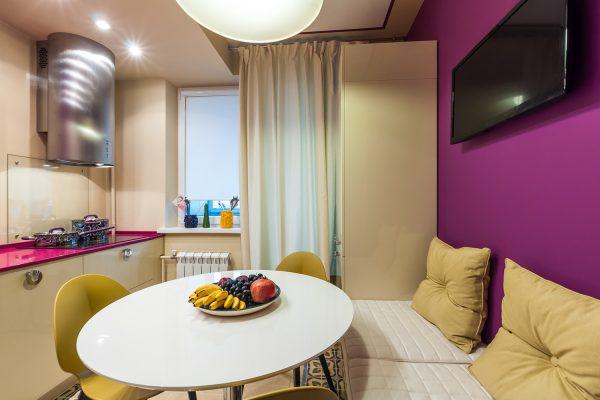 комфортный диван с бежевыми подушками у пурпурной стены